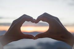 A mulher que faz a forma do coração durante a elevação do sol, deus é conceito do amor, forma do coração, turismo da montanha, sí fotografia de stock royalty free