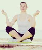 Mulher que faz a ioga de pernas cruzadas Imagens de Stock