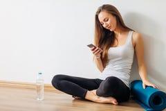 Mulher que faz a ioga e que usa o telefone celular que senta-se no assoalho foto de stock