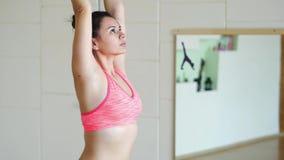Mulher que faz a ioga em esteiras do exercício no salão da aptidão, fim acima video estoque