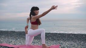 Mulher que faz a ioga em uma costa na manhã video estoque