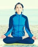 A mulher que faz a ioga levanta de pernas cruzadas na praia na manhã Imagem de Stock