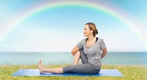 Mulher que faz a ioga na pose da torção na esteira imagem de stock