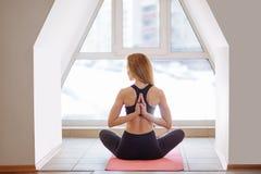 Mulher que faz a ioga na pose reversa da oração Pashchima Namaskarasana fotografia de stock