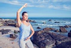 Mulher que faz a ioga na praia fotos de stock