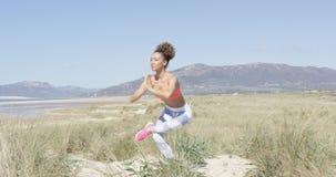 Mulher que faz a ioga na praia video estoque