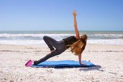 Mulher que faz a ioga na praia na prancha lateral Foto de Stock