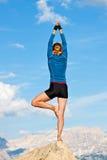 Mulher que faz a ioga na rocha fotografia de stock royalty free