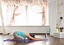 Mulher que faz a ioga no assoalho Foto de Stock