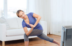 A mulher que faz a ioga o baixo ângulo investe contra a pose na esteira Foto de Stock