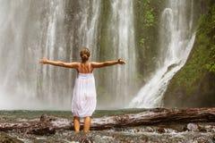 Mulher que faz a ioga perto da cachoeira Fotos de Stock
