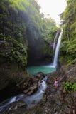 Mulher que faz a ioga perto da cachoeira Foto de Stock