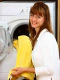 Mulher que faz a lavanderia com sorriso fotos de stock