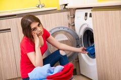 A mulher que faz a lavanderia em casa fotografia de stock royalty free
