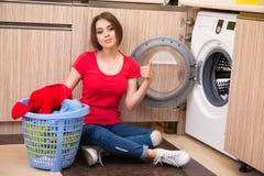A mulher que faz a lavanderia em casa fotografia de stock