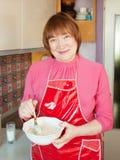 A mulher que faz a massa de pão com whisk foto de stock royalty free