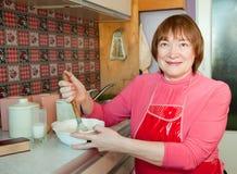 A mulher que faz a massa de pão com whisk imagem de stock