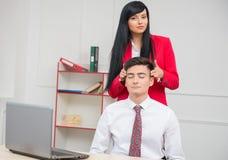 Mulher que faz a massagem a seu colega no escritório Foto de Stock Royalty Free