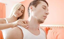 Mulher que faz massagens ombros do homem fotografia de stock
