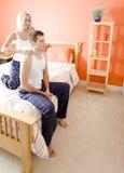 Mulher que faz massagens ombros do homem no quarto imagem de stock royalty free