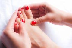 Mulher que faz massagens seu pé imagens de stock