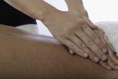 Mulher que faz massagens um homem novo imagem de stock