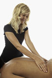 Mulher que faz massagens um homem novo imagens de stock royalty free