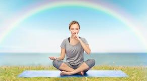 Mulher que faz a meditação da ioga na pose dos lótus na esteira Imagem de Stock