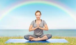Mulher que faz a meditação da ioga na pose dos lótus na esteira Imagens de Stock