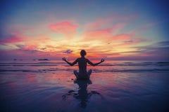 Mulher que faz a meditação perto da praia do oceano Foto de Stock Royalty Free