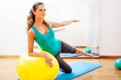 A mulher que faz o corpo exercita em uma bola amarela foto de stock royalty free