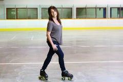 Mulher que faz o cruzamento em patins de rolo do quadrilátero Fotografia de Stock