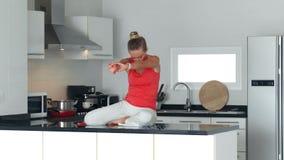 A mulher que faz o esticão exercita o assento na mesa de cozinha para relaxar vídeos de arquivo