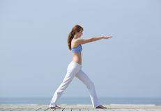 Mulher que faz o estiramento da ioga na praia Fotografia de Stock Royalty Free