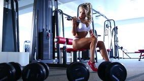 Mulher que faz o exercício com o barbell no gym filme