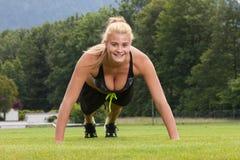 A mulher que faz o exercício da aptidão levanta exterior Fotografia de Stock