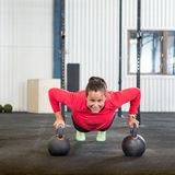 Mulher que faz o exercício da flexão de braço com Kettlebell Imagens de Stock Royalty Free