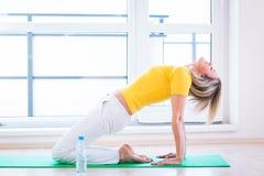 Mulher que faz o exercício da IOGA em casa Fotografia de Stock