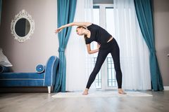 Mulher que faz o exercício da IOGA em casa Exercício da manhã no quarto Estilo de vida saudável e do esporte imagens de stock