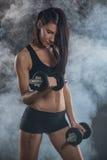 Mulher que faz o exercício do bíceps fotografia de stock royalty free