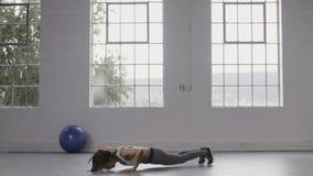 Mulher que faz o exercício do burpee no estúdio da aptidão video estoque