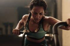 Mulher que faz o exercício intenso na bicicleta do gym imagem de stock