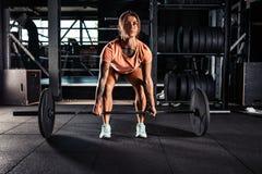 Mulher que faz o exercício pesado do deadlift no gym foto de stock