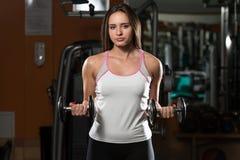 Mulher que faz o exercício pesado para o bíceps Fotografia de Stock