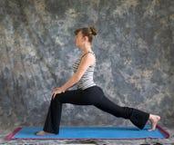 Mulher que faz o pose elevado do Lunge da postura da ioga Imagem de Stock Royalty Free