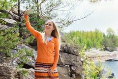 Mulher que faz o selfie fora sobre o rio azul Fotografia de Stock Royalty Free