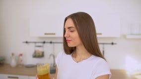 Mulher que faz o suco de maçã no juicer e que bebe o fresco em casa na cozinha Juicing e mulher feliz comendo saudável vídeos de arquivo