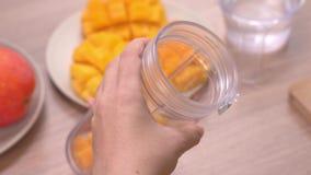 Mulher que faz o suco fresco da manga na cozinha do verão no fundo de madeira brilhante da tabela Conceito caseiro saudável video estoque