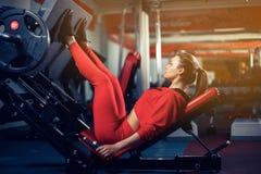 Mulher que faz o treinamento da aptidão em uma máquina do impulso da extensão do pé com pesos Foto de Stock Royalty Free