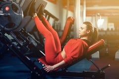 Mulher que faz o treinamento da aptidão em uma máquina do impulso da extensão do pé com pesos Fotografia de Stock Royalty Free